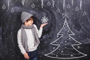 pojke som håller en snöflinga på armen foto