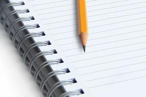 bild av en anteckningsbok och penna på vit bakgrund, närbild foto