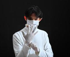 läkare tar på sig en latexhandske. foto