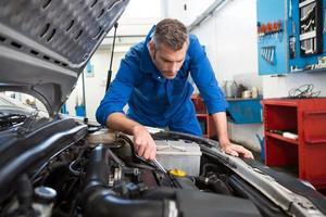 mekaniker undersöker under huven på bilen foto