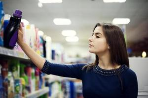 kvinna som väljer tvättmedel i snabbköpet foto