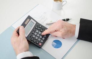 affärsman händer med miniräknare foto