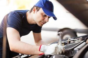 mekaniker som arbetar på en bilmotor foto