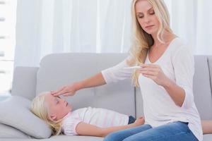 mamma som mäter temperaturen på sin dotter foto