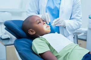 pojke som har sina tänder undersökta av tandläkaren foto