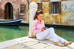 kvinna sitter på gatan och kontrollerar foton i Venedig