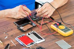 närbild av handreparation mobiltelefon foto