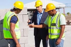 byggnadsarbetare med deras chef som kontrollerar tegelstenar foto