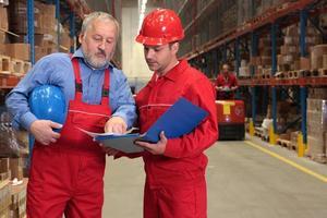 två arbetare som granskar papper i lager foto