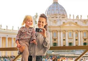 mamma och bebisflicka som kontrollerar bilder i Vatikanstaten