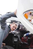 inspektör kontrollerar arbetande motor på vit stor rigg semi truck foto