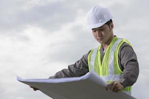 asiatisk industriell ingenjör på jobbet och tittar på planer. foto