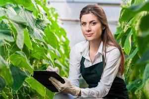 porträtt av en ung kvinna på jobbet i växthus foto