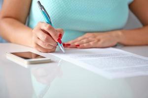 ung kvinna tecknar ett kontrakt foto