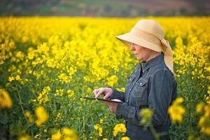 kvinnlig jordbrukare med digital tablet i odlad rapsfrö