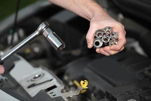 bilmekaniker med förkromad skiftnyckel i närbild foto