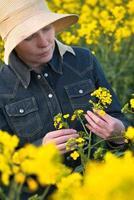 kvinnlig jordbrukare i rapsfrö odlat jordbruksfält