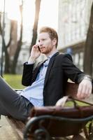 affärsman som sitter på en bänk och pratar i telefon foto