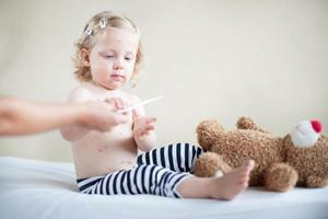 kontrollera barnets temperatur foto