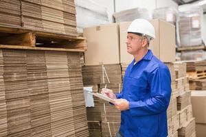 lagerarbetare som kontrollerar sin lista på urklipp