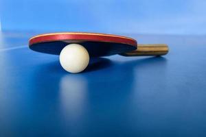 pin-pong gummi och en boll på blå spelbräda foto