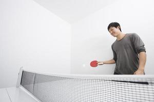 asiatisk mitten av vuxen man som spelar ping-pong foto