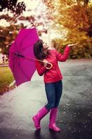 glad kvinna med paraply som kontrollerar för regn i en park foto