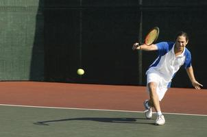 tennisspelare som slår bakhand foto