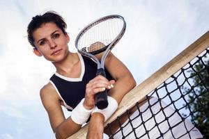 ung flicka som spelar tennis vid det vackra vädret foto