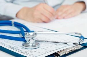 läkare som arbetar vid skrivbordet. närbild av stetoskop