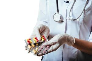 ung och vänlig kvinna läkare håller erbjudande piller isolerad på foto
