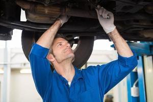 mekaniker undersöker under bilen foto