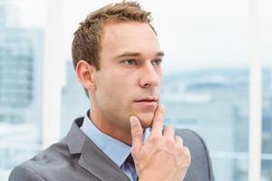 tankeväckande ung affärsman tittar bort foto