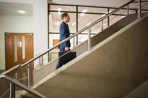 affärsman som klättrar uppför trappan foto