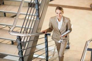 ung affärskvinna som går uppför trappan foto