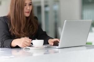 asien ung affärskvinna på café med laptop och kaffe foto