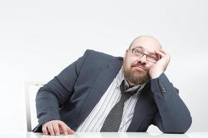 fundersam affärsman som sitter vid bordet. foto