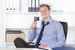 ung leende man dricker en kopp kaffe foto