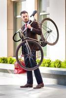 stilig affärsman som bär sin cykel foto