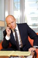 affärsman som pratar i mobiltelefon medan du läser tidningen foto