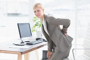sorglig affärskvinna med ryggsmärta foto