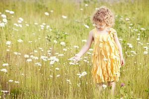 vacker flicka som går i fält av blommor.