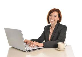 glad affärskvinna med rött hår som dricker kaffe och ler foto