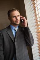 affärsman som kikar genom persienner när han är på samtal foto