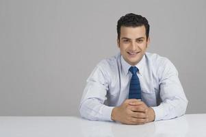 affärsman som ler med knäppta händer foto
