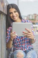 företag vacker leende brunett kvinna med en surfplatta foto