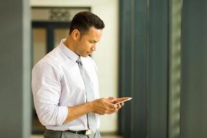 medelålders affärsman som smsar på sin smarta telefon foto