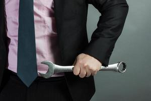 affärsman håller skiftnyckel i handen
