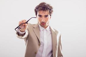 arg man i kostym som tar bort sina glasögon. foto