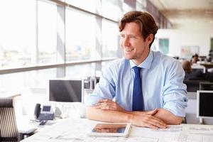manlig arkitekt vid sitt skrivbord på ett kontor och tittar bort foto